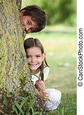 Two little children hiding behind tree
