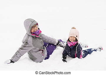 Two little children playing in snow