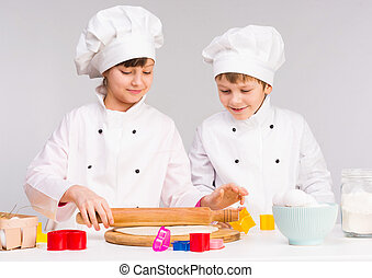 two little cooks rolling out a dough