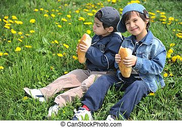 Two little friends eating together, outdoors