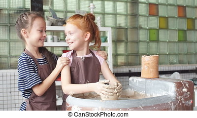 Two little girl having fun playing with clay on a pottery...