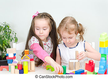 Two little girl playing with building blocks
