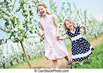 Two little girl run and having fun in spring garden