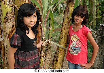 two little girl stand up beside the tree