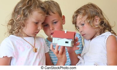 two little girls and boy with toy house indoor
