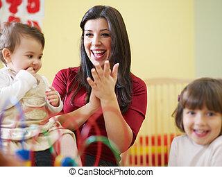 two little girls and female teacher in kindergarten - female...