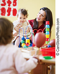 female toddler and 2-3 years girl playing with maraca in kindergarten. Vertical shape