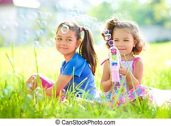 Two little girls are blowing soap bubbles