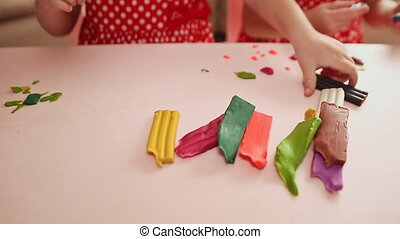 Two little girls are engaged in molding plasticine at the table. Hands of children close-up.
