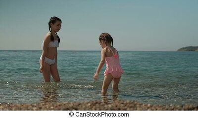 Two little girls are playing in the water on the sunny beach.