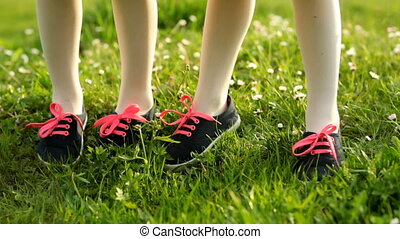 Two little girls are standing on green grass.