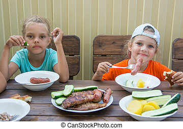 Two little girls at a wooden table in nature eating grilled sausages