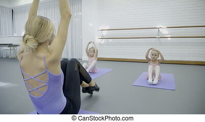 Two little girls at class in ballet school.