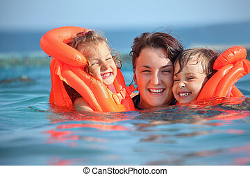 two little girls bathing in lifejackets with young woman in pool on resort