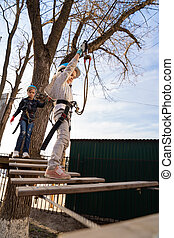 two little girls climb in rope Park in the spring