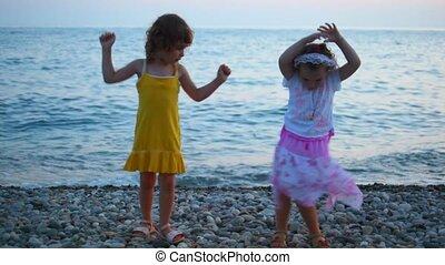 two little girls dancing in evening pebble beach, sea in...