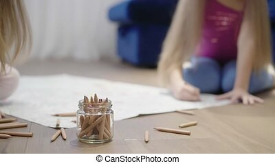 Two little girls drawing a large picture on the floor using pencils blur