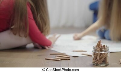 Two little girls drawing a large picture on the floor using pencils