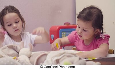 Two little girls drawing at a table 4K