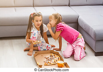 Two little girls eating huge pizza at home