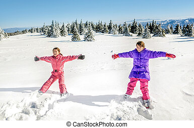 Two Little girls falling and having fun on the snow