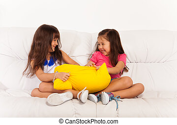 Two little girls fighting over pillow