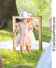 Two little girls holding a painting frame