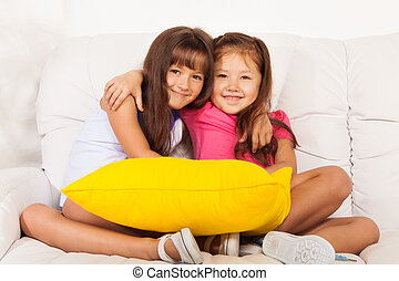 Two little girls hugging with pillows