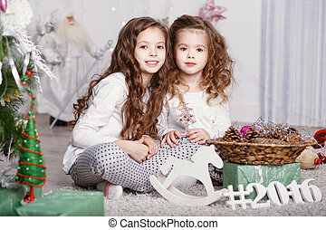 Two little girls in a comfortable home clothes sitting on the floor in the beautiful Christmas decorations.