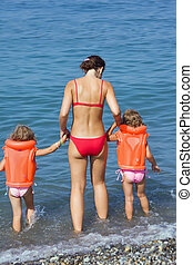 two little girls in lifejackets with young woman coming into sea