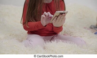 Two little girls in pajamas using smartphones on bed