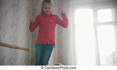 Two little girls jumping on the bed