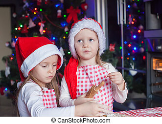Two little girls make gingerbread cookies for Christmas at home