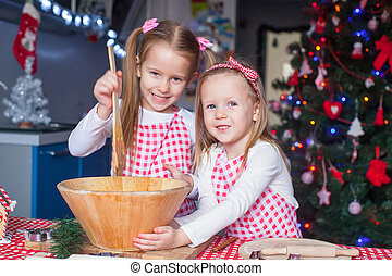 Two little girls make gingerbread cookies for Christmas