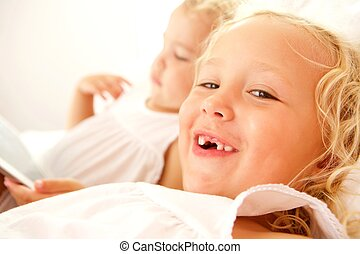 Two little girls on bed at home