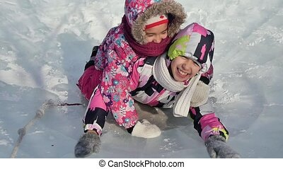 Two little girls playing and having fun on ice in winter park