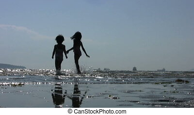 A shot of two adorable little girls playing and dancing in the surf on a beautiful summer day at the beach.