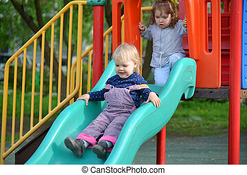 Two little girls playing on  playground