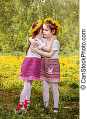 Two little girls playing on the meadow