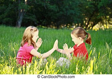 Two little girls playing patty-cake