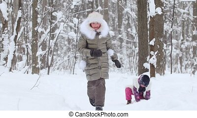 Two little girls playing snowballs in winter forest.