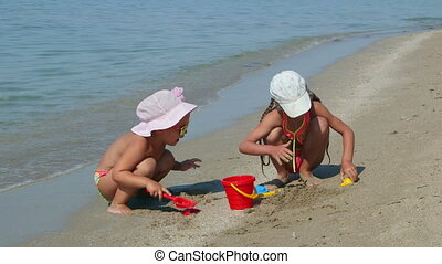 Two little girls playing with children toys on sand beach in surf