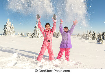 Two Little girls playing with snow and  having fun