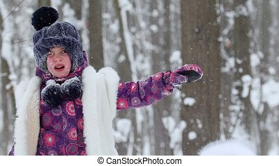 Two little girls playing with snow on the in winter forest. Snow on girls face