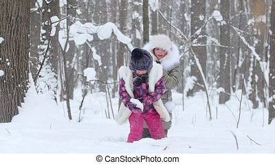 Two little girls playing with snow on the in winter forest.