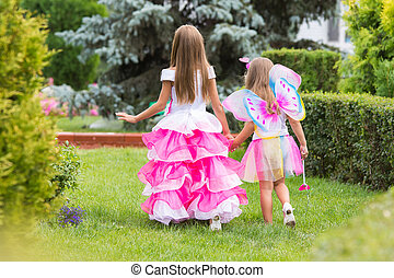 Two little girls, princess and fairy strolling through the garden