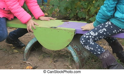 Two little girls riding on swing outdoors - Two little girls...