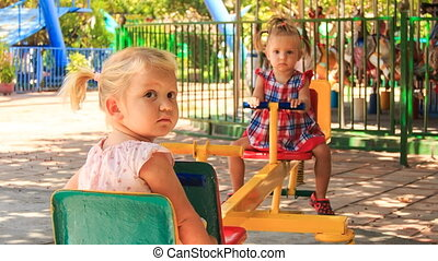 two little girls rock on swing on play ground in tropical park