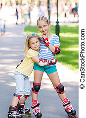 Two little girls rollerskating in the park