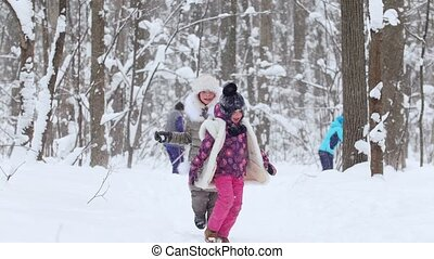 Two little girls running and playing snowballs in winter forest.